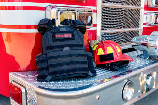 Ballistic vest and red firefighter helment on fire truck bumper. Concept of evolving role of fire department response to mass casualty shooting and terrorism stock photo