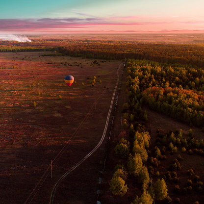 Beautiful blue-yellow-red balloon against the background of a field and forest on the horizon at sunset. Hot air balloon. Aerial view. From above