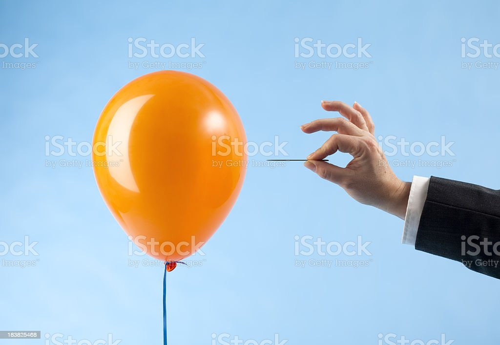"""Balloon attacked by hand with needle """"Orange balloon and arm in suit approaching it with a needle, ready to burst the bubble. Concept for loss, catastrophic failure. Blue background."""" Balloon Stock Photo"""