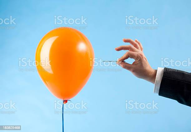 Balloon Attacked By Hand With Needle Stock Photo - Download Image Now