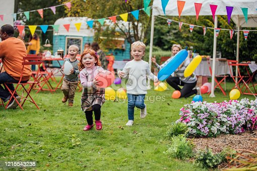 Three young children enjoy playing with balloons at a garden party as they run towards the camera. Adults are sat talking in the background and looking at the children. There is a food truck in the background and a marquee and colorful bunting fill the garden.