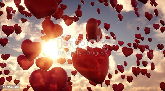 A group of heart-shaped balloons flying through the air on a cloudy sky background. The hearts appear transparent in a red hue and have a slightly marbled surface.