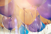 Balloon in birthday party background.Multi colour (yellow,blue,violet,purple) helium Ballon with string and ribbon in celebrate wedding day.Concept of balloon in wedding and birthday party.