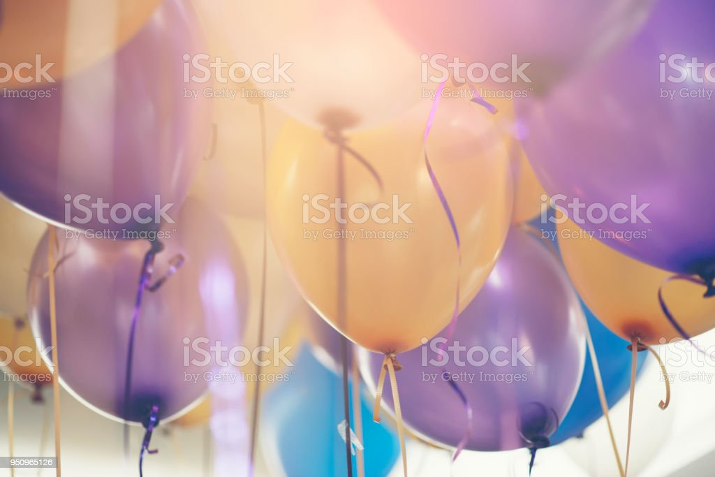 Balloon in birthday party background.Multi colour (yellow,blue,violet,purple) helium Ballon with string and ribbon in celebrate wedding day.Concept of balloon in wedding and birthday party. stock photo