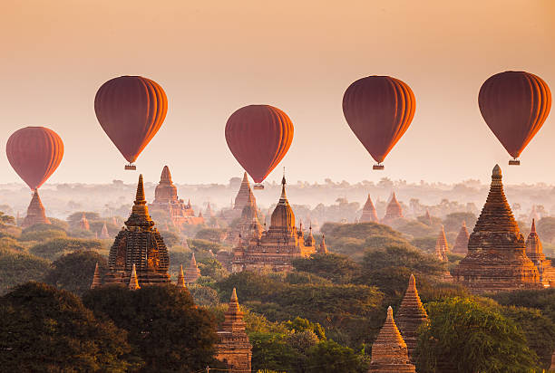 Balloon over plain of Bagan in misty morning, Myanmar Bagan is an archaeological zone of more than 2,000 ancient pagodas. It was built in 11th centuries during the rise of Bagan empire.Today Bagan is a part of Mandalay division, Myanmar. pagoda stock pictures, royalty-free photos & images