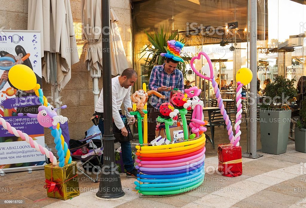 Balloon twisters specializing in entertaining events promoting themselves. stock photo