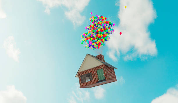 Balloons attached to a house makes it fly away up in the air stock photo