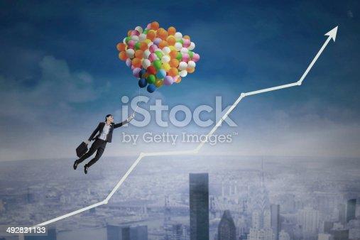 istock Balloons carrying a woman over an upward arrow 492821133