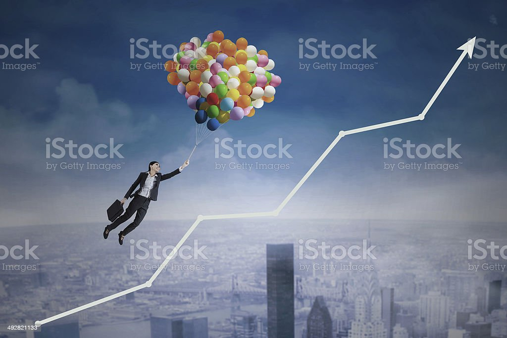 Balloons carrying a woman over an upward arrow stock photo