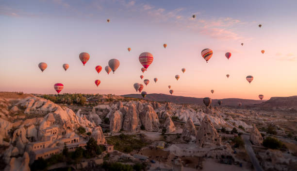 Balloons filled with tourists float at sunrise above the cones of the old village stock photo