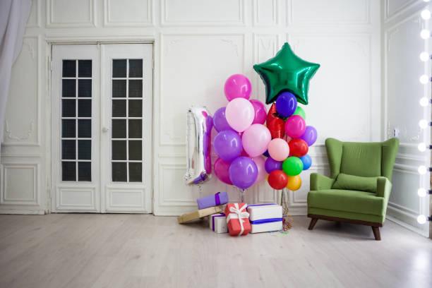luftballons in verschiedenen farben mit geschenken für den urlaub in einem raum - partyraum stock-fotos und bilder