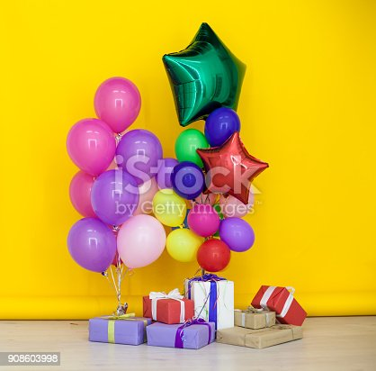 815229514 istock photo balloons of different colors with gifts for the holiday 908603998