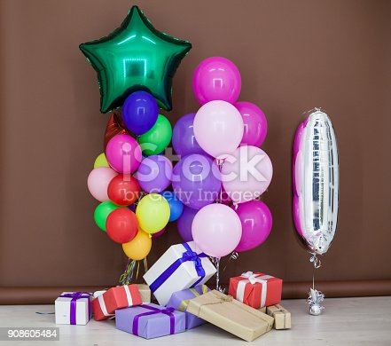 815229514 istock photo balloons of different colors with gifts for the holiday 908605484