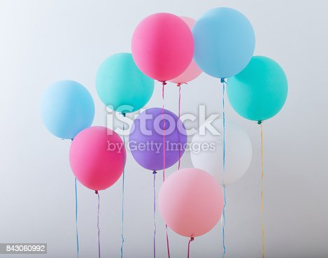 istock balloons on white wooden background 843060992