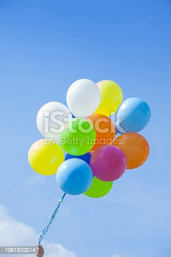 Colorful ballons bouquet over a clear sky. Outdoors photography. Low angle view. Focus on foreground. Copy space. Close-up.