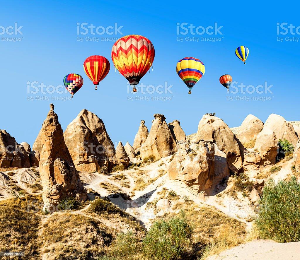 Balloons over the volcanic mountain landscape of Cappadocia stock photo
