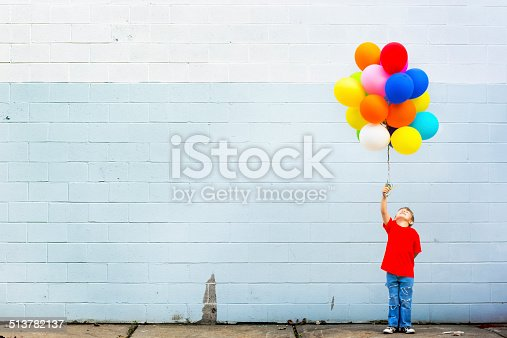 Little boy standing against the wall with a lot of colorful balloons.