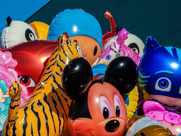 positionsnummern mit der form von comic-figuren zum verkauf bei einem konzert einer band für kinder, mit mickey mouse, catboy aus pj masken und andere - disney dekorationen stock-fotos und bilder