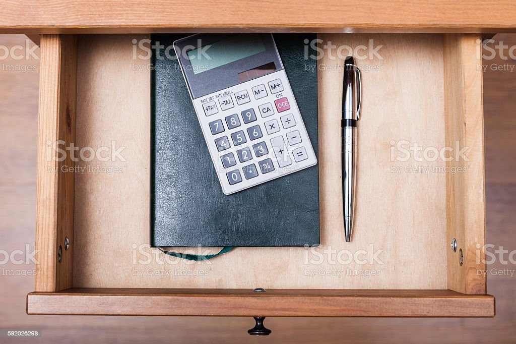 ballpen, calculator and notebook in open drawer stock photo