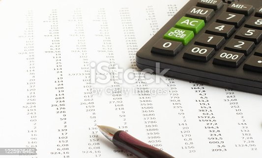 Ballpoint ink calculator and pen on a financial spreadsheet statement with columns of numbers.