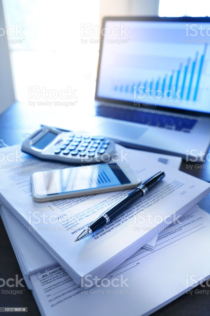 Ballpoint Pen A Mobile Phone And A Calculator Resting On Top Of Stack Of Documents stock photo