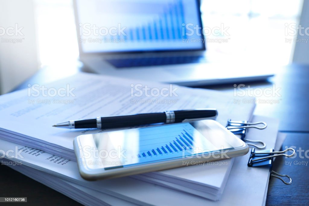 Ballpoint Pen And A Mobile Phone Resting On Top Of Documents To Sign stock photo