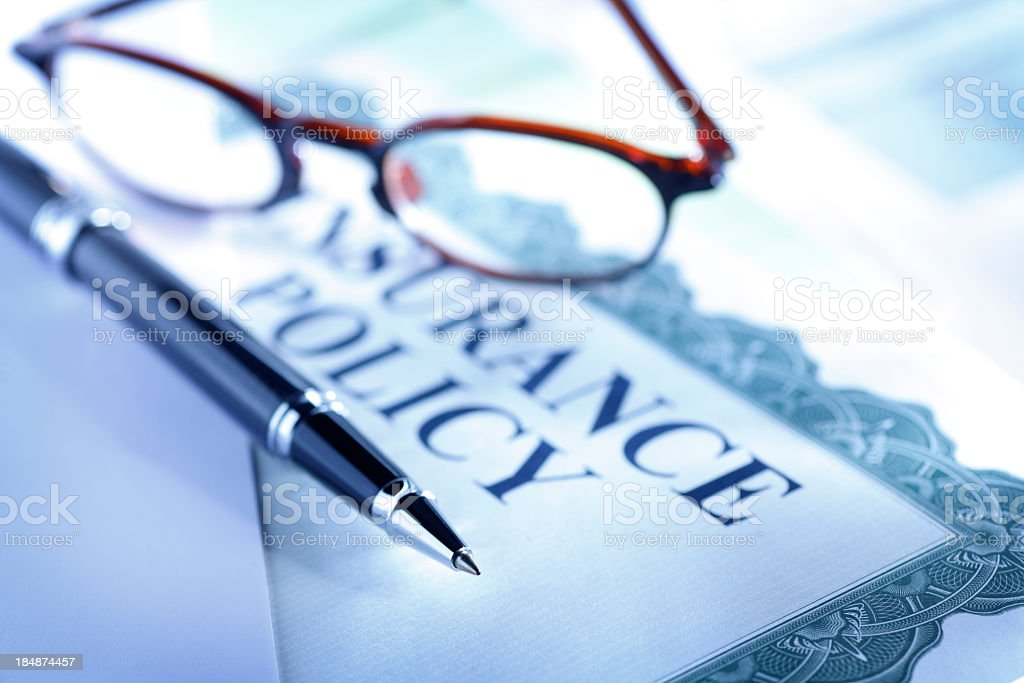 Ballpoint pen and eyeglasses on top of insurance policy stock photo