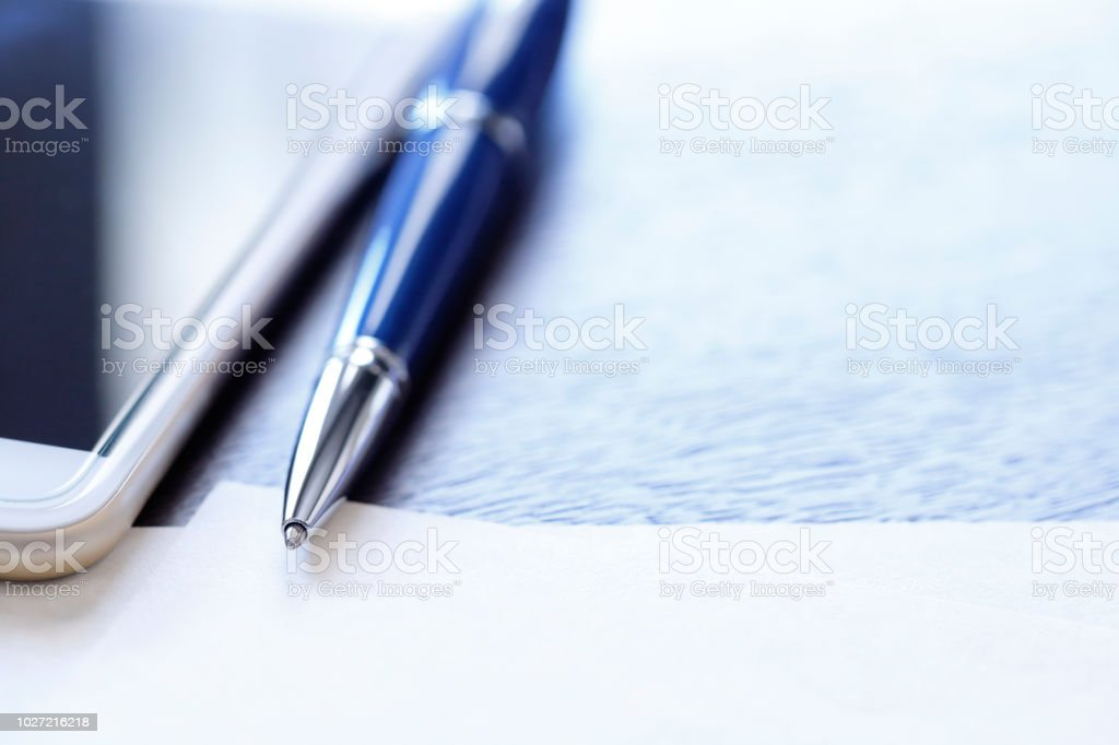 A ballpoint pen and a mobile phone rest on top of a blank sheet of...