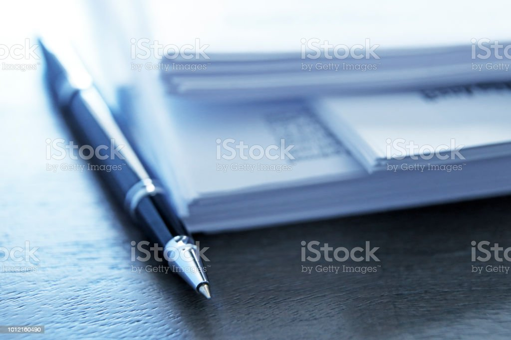 A ballpoint pen rests next to a stack of documents ready for signing....