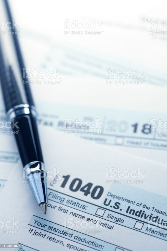 A ballpoint pen used to sign a return rests on top of an IRS 1040 tax...