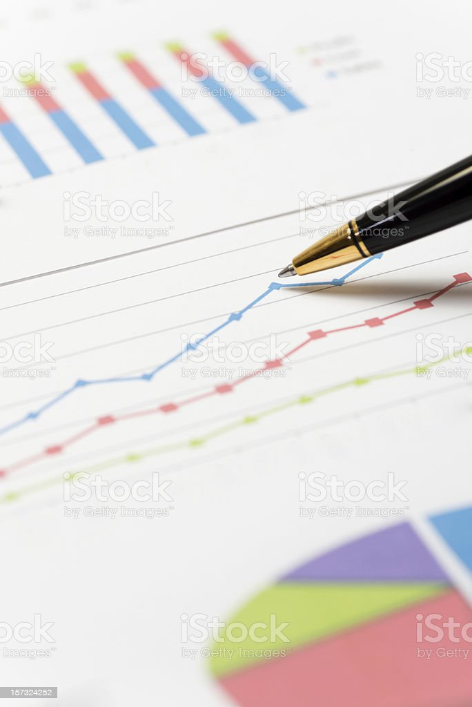 Ballpoint pen pointing to business graphs stock photo