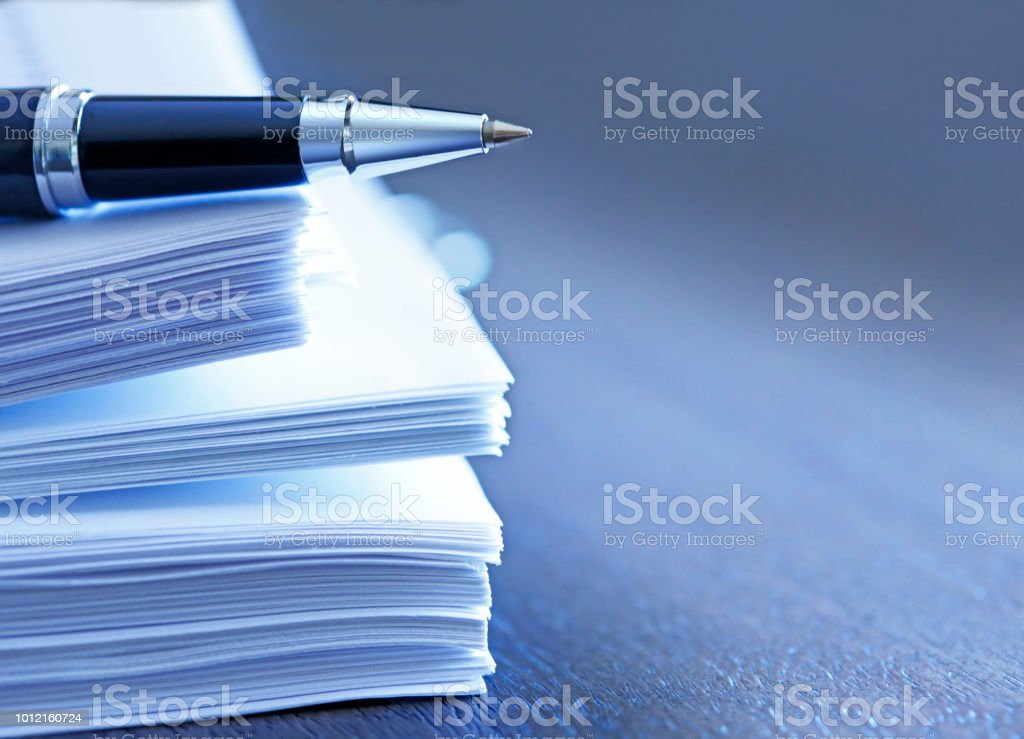 Ballpoint Pen Resting On Top Of Stack Of Documents stock photo