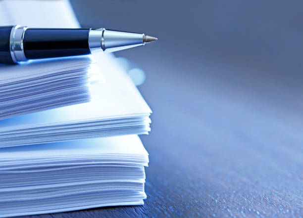 ballpoint pen resting on top of stack of documents - rapporto foto e immagini stock