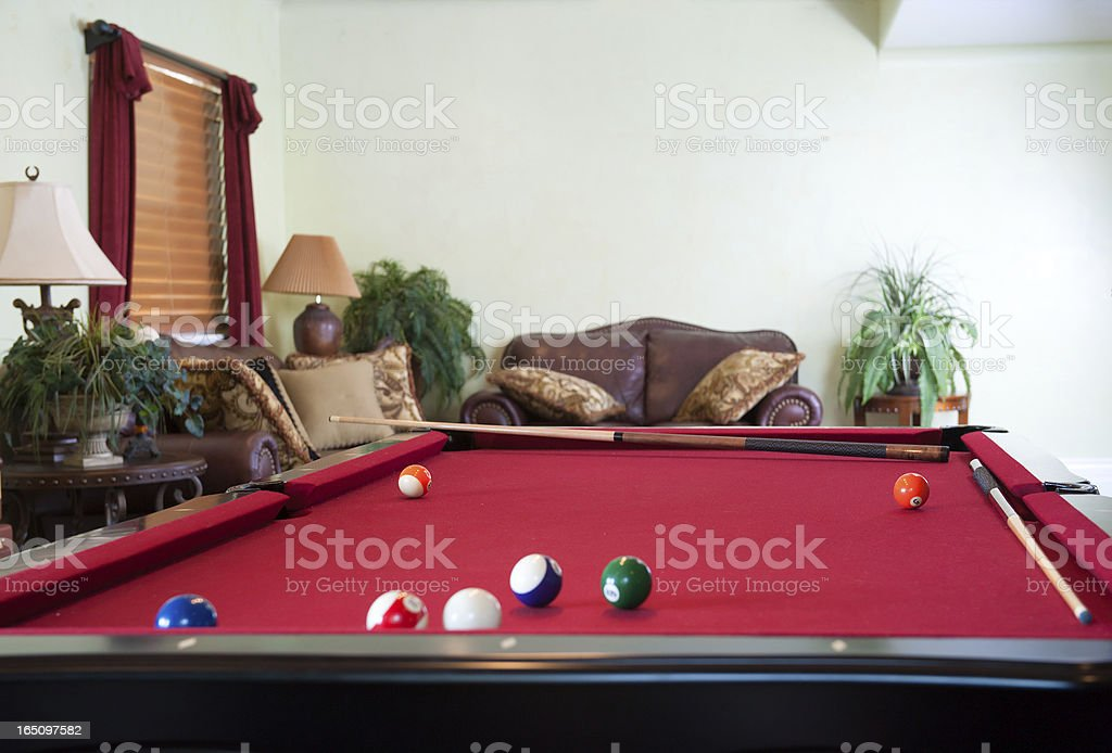 Balls  and cues on pool table in game room stock photo
