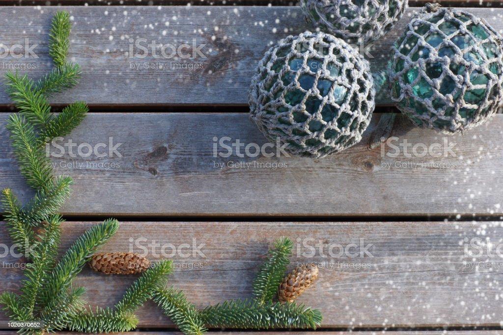 Balles en un filet sur un fond en bois avec une branche d'épinette et cônes - Photo