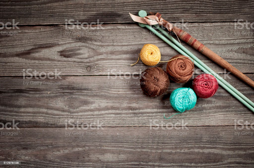 balls of colored iris yarn on wooden boards stock photo