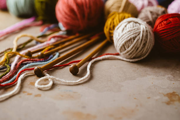 balls of wool and knitting needles - wool stock photos and pictures