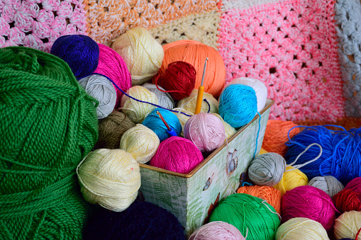 Balls of yarn in a basket with colorful crochet background