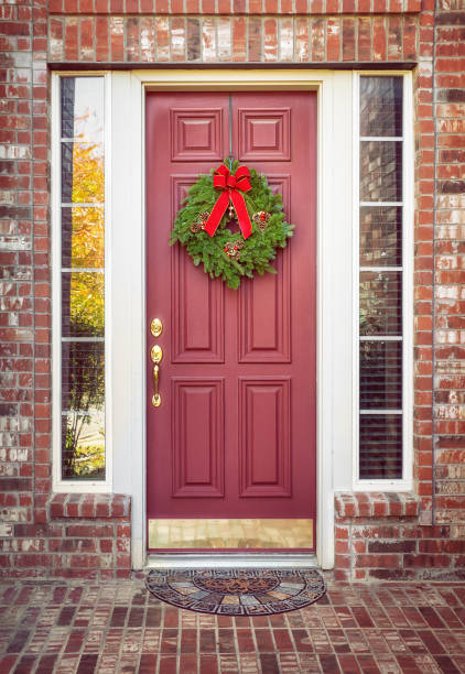 balsam-tanne adventskranz auf eine rote tür - deko hauseingang weihnachten stock-fotos und bilder
