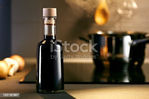 Vinegar in front of hob with steaming pot