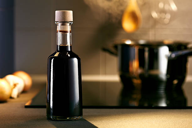 Balsamic vinegar bottle in a kitchen Vinegar in front of hob with steaming pot balsamic vinegar stock pictures, royalty-free photos & images