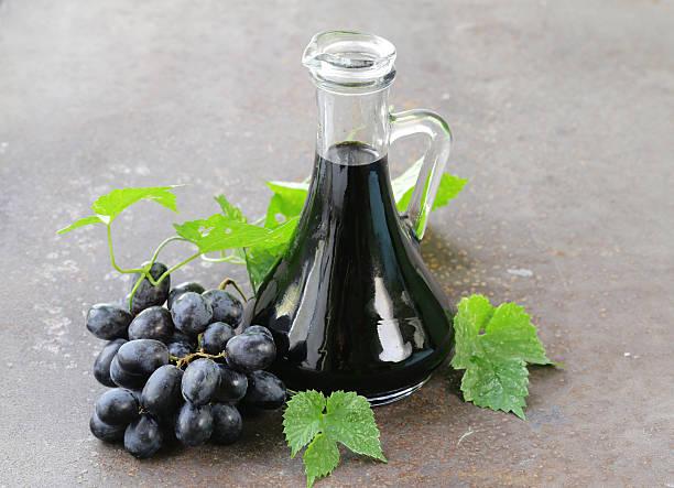 Aceto balsamico di una Brocca di vetro e uva - foto stock