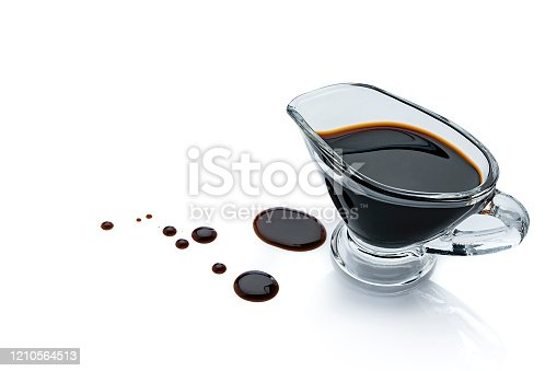 High angle view of balsamic vinegar in a gravy boat isolated on reflective white background. Some vinegar drops are spilled on the background beside the container. The composition is at the right of an horizontal frame leaving useful copy space for text and/or logo at the left. Predominant colors are black and white. High resolution 42Mp studio digital capture taken with Sony A7rII and Sony FE 90mm f2.8 macro G OSS lens