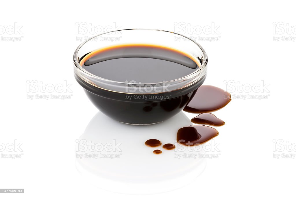 Balsamic vinegar in glass bowl with spills isolated on white stock photo