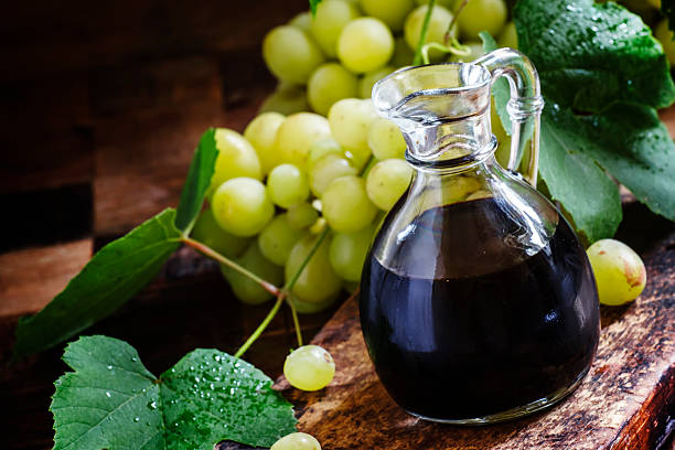 Balsamic vinegar Balsamic vinegar in a glass jug, vintage wooden background, rustic style, selective focus balsamic vinegar stock pictures, royalty-free photos & images