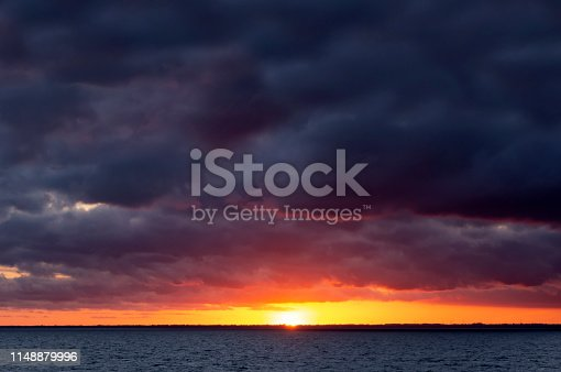 Sunset over the Baltic Sea coast with dark clouds and bright sun setting on the horizon.