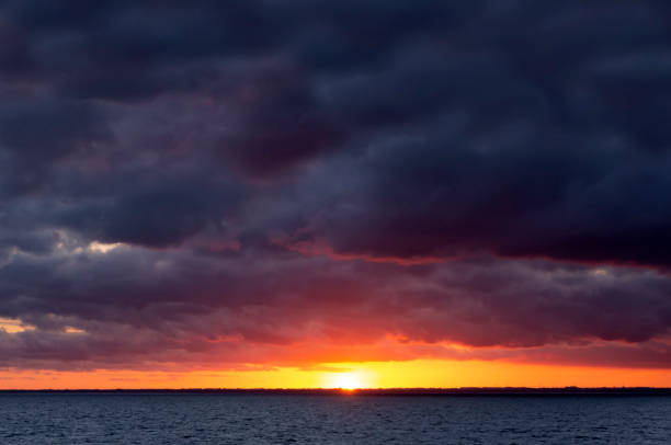 Baltic sunset with dark clouds stock photo