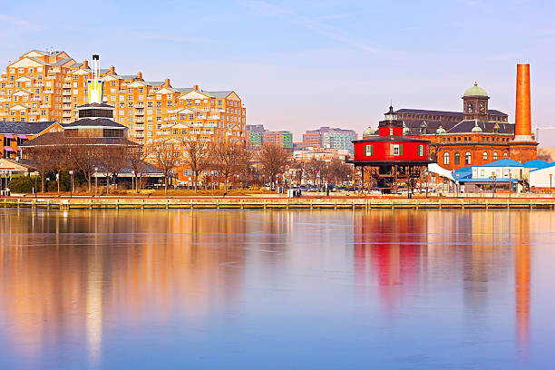 Baltimore harbor and the Seven Foot Knoll Lighthouse at sunset. Colorful reflections of waterfront buildings at Inner Harbor in Baltimore, Maryland. inner harbor baltimore stock pictures, royalty-free photos & images