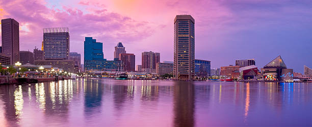 Baltimore Inner Harbor Amazing Sunset with Reflections on Water Panorama Panoramic image of Baltimore's Inner Harbor at sunset. The brilliant colors of the sky, buildings and harbor lights are refecting on the calm water. inner harbor baltimore stock pictures, royalty-free photos & images