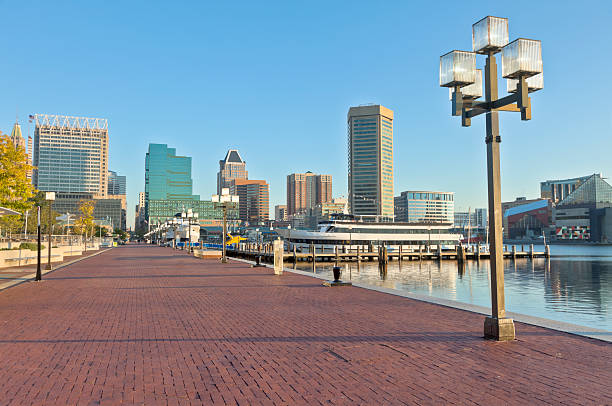 Baltimore Inner Harbor Skyline and Paved Waterfront Promenade The skyline and red-brick paved Waterfront Promenade along Baltimore's Inner Harbor in the early morning. Lamps adorn the harbor's edge. inner harbor baltimore stock pictures, royalty-free photos & images